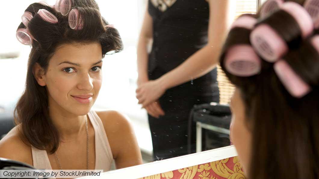 Lockenwickler im Haar einer Kundin beim Friseur in Graz