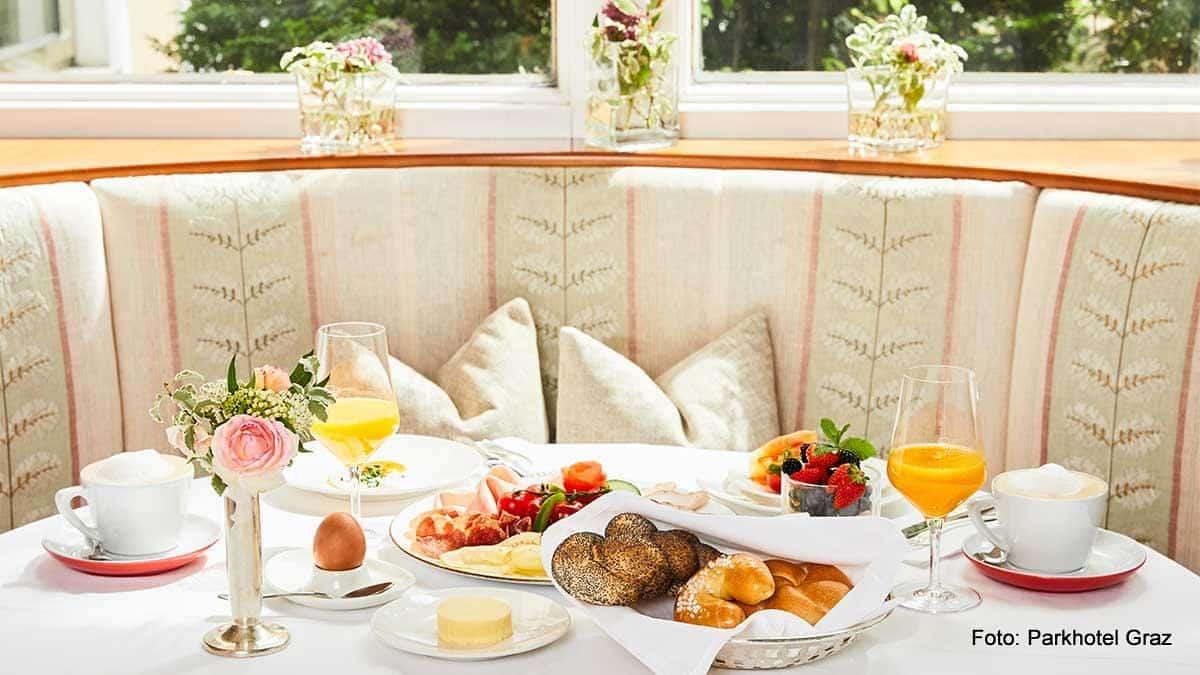 Gedeckter Frühstückstisch im Parkhotel Graz mit Gebäck, Ei, Orangensaft, Cappuccino, Wurst und Käseteller