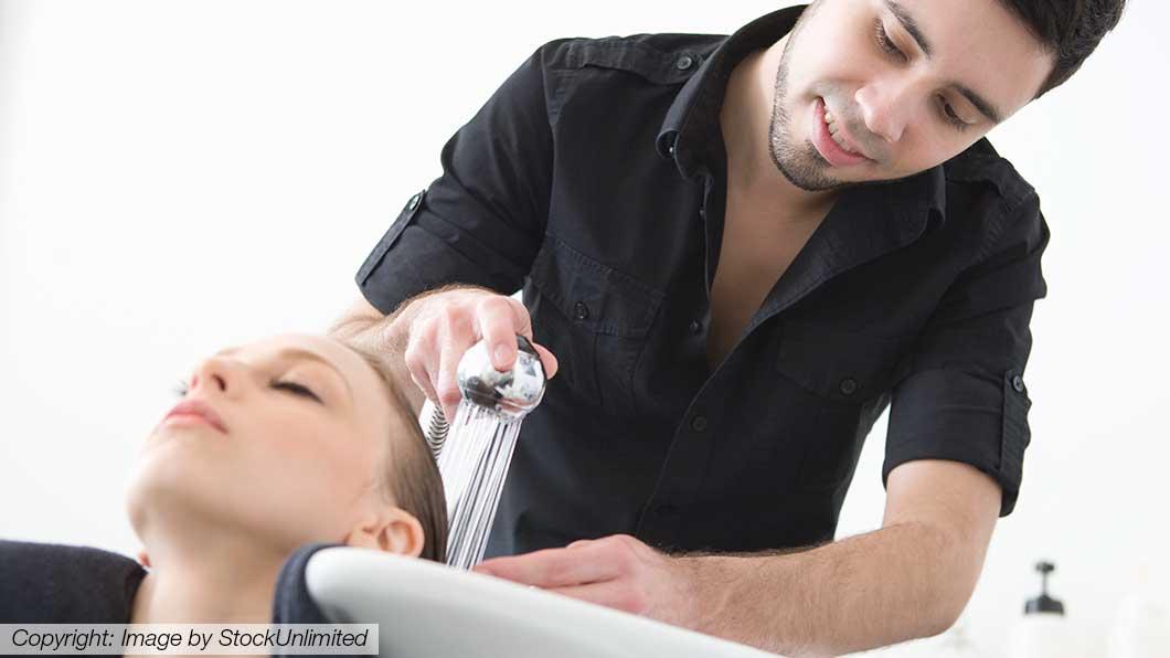 Friseur wäscht die Haare einer Kundin